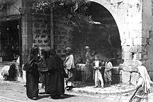 From left to right: A boy staring out from a store's window sill beneath which a lamb is walking by; three fully veiled women conversing on the street; beneath an olive grove jutting out of a large stone archway and beside a fountain, a man is walking, a woman is collecting water from the fountain, and two young boys are standing and smiling; a young girl walking on the street