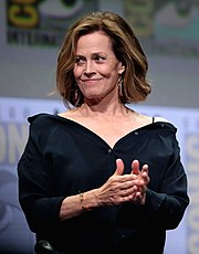 A smiling, formally-dressed Sigourney Weaver