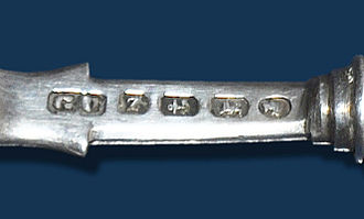 Hallmark - A set of hallmarks on an English silver spoon. From left to right, the maker's mark of George Unite, the date letter (1889), the Birmingham Assay Office mark, the lion passant and the monarch's head tax-mark