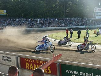 Track racing - Speedway riders powersliding around a corner