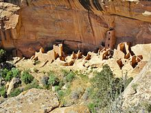 A color picture of a large sandstone ruin under an alcove