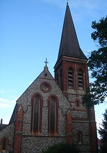 Front-on view of a pale flint and red brick church in low light, with a tower and tall spire prominent on the right. On the left, two tall, narrow round-headed windows and a round window dominate. The tower has paired louvres below the spire.