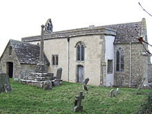 A small stone church seen from the southeast with a porch to the left, a protruding rendered south aisle in the middle, and a short chancel to the right. On the west gable is a bellcote, and in front of the church is a churchyard cross