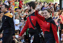 People wearing Star Trek: the Next Gneration uniforms in a parade.