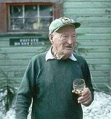 Color picture; An elderly man holding a glass and wearing a hat stands in front of a wooden lodge.