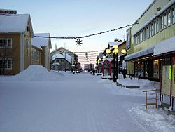 The main street (Storgatan) and December 2005 snow and Christmas lights in Gällivare at about noon.