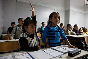 Children at desks in a classroom.  One child raises her hand.