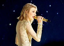 Swift actuando en The 1989 World Tour.  Se la ve con cabello corto y un traje brillante mientras agarra un micrófono dorado.