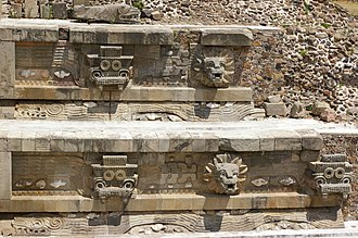 """Temple of the Feathered Serpent, Teotihuacan - Detail of the pyramid, showing the alternating """"Tlaloc"""" (left) and feathered serpent (right) heads. Note the long undulating feathered serpents in profile under the heads."""