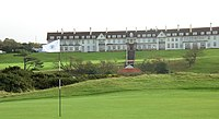 A golf course.  In the background is the Turnberry Hotel, a two-story hotel with white façade and a red roof. This picture was taken in Ayrshire, Scotland.