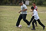 U.S. Air Force Staff Sgt. Faber Piedrahita, a vehicle maintenance journeyman with the 376th Expeditionary Logistics Readiness Squadron, plays soccer with students at the Ozyornoe School in Kyrgyzstan Sept 120903-F-KX404-064.jpg