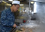 U.S. Navy Airman Catherine Burgess grills pork chops in the chief's mess aboard the aircraft carrier USS Nimitz (CVN 68) 130110-N-TR165-009.jpg