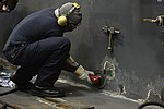 U.S. Navy Aviation Boatswain's Mate (Handling) 3rd Class Corey Collins uses an abrasive grinder to prepare a bulkhead for a coat of primer in the hangar bay aboard the amphibious assault ship USS Bataan 131003-N-HO612-059.jpg