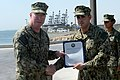 U.S. Navy Vice Adm. John W. Miller, left, commander of U.S. Naval Forces Central Command, U.S. 5th Fleet, Combined Maritime Forces, presents Master-at-Arms 2nd Class Luis Gomez, assigned to Commander Task Group 130828-N-DY265-059.jpg