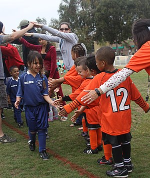 Sportsmanship - These two teams of young soccer (football) players line up and high-five after a game to learn about good sportsmanship