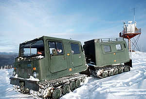 Bandvagn 206 - This tracked vehicle, a Swedish Hägglunds Bv206, achieves low ground pressure through full-length, wide rubber tracks and a lightweight body. The two sections of the vehicle are articulated, allowing it to keep contact with the ground over broken terrain. The ground pressure is low enough that the vehicle can traverse loose snow without sinking. The vehicle is amphibious and propelled in water by its tracks.