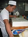US Navy 040315-N-5573G-001 Culinary Specialist 1st Class Jonathan C. Villanueva traces the Seventh Fleet command logo onto a cake.jpg
