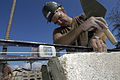 US Navy 050310-N-0411D-013 Builder 2nd Class Tom Hurlburt assigned to Naval Mobile Construction Battalion One (NMCB-1), levels a block of the school building wall which he and fellow Seabees are building in Gonaives, Haiti.jpg