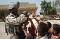US Navy 060619-N-8252B-080 Sgt. Jontele Harrison assigned to Company B, 2nd Battalion, 8th Infantry Regiment, 2nd Brigade Combat Team, 4th Infantry Division, hands out candy to local children during a dismounted patrol through.jpg