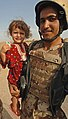 US Navy 060816-N-4097B-030 An Iraqi army soldier from 3rd Battalion, 3rd Brigade, 5th Iraqi Army Division holds a small girl during a visit to a village outside Mujahida, Iraq.jpg