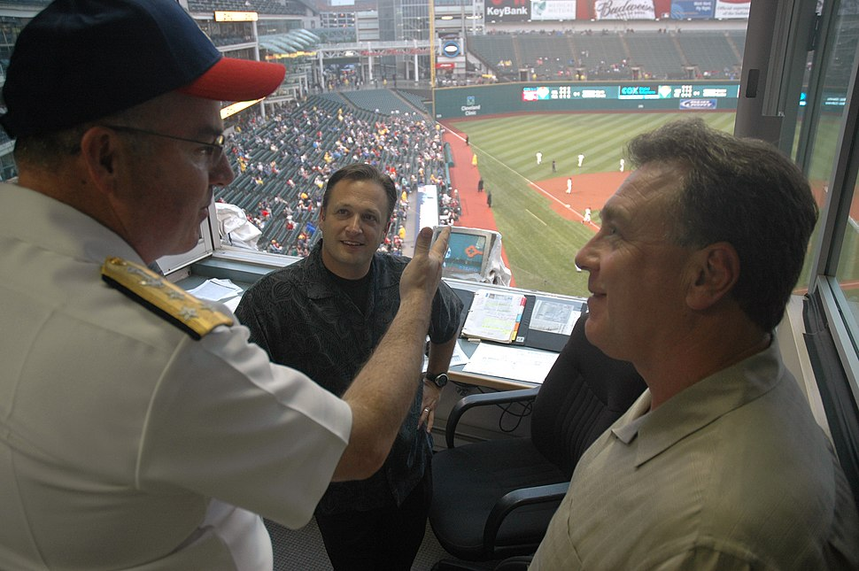 US Navy 060828-N-1805P-007 Chief of Naval Personnel Vice Adm. John C. Harvey Jr. chats with broadcasters from Cleveland radio station WTAM 1100 AM during a Major League Baseball game at Jacobs Field between the Cleveland Indian