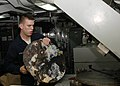 US Navy 061024-N-5243R-004 A culinary specialist seaman assigned to the supply department aboard USS Essex (LHD 2) pulls a disc of compressed plastic from the Plastic Processor Compress Melt Unit located in the ship's Plastic's.jpg