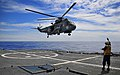 US Navy 100303-N-4774B-050 Boatswain's Mate 3rd Class Elan Landin signals to an approaching Brazilian navy SH-3 Sea King helicopter during a joint maritime exercise with the Brazilian navy.jpg