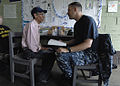 US Navy 100917-N-7656R-036 Lt. Cmdr. Tyler Miles, embarked aboard the multi-purpose amphibious assault ship USS Iwo Jima (LHD 7), talks to a patien.jpg