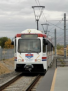 A white and red train with the driver visible approaches a station. The overhead wires powering the train are visible with overcast skies and mountains providing the backdrop.