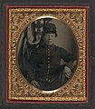 Unidentified soldier in Union artillery uniform sitting in front of American flag LOC 5228559561.jpg