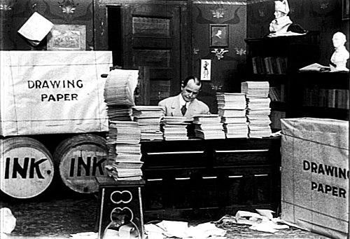 Маккей сидит в центре в окружении огромных стопок бумаги и бочек с чернилами.