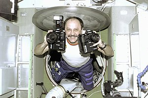 Yury Usachov - Usachev floats into the Zvezda Service Module equipped with cameras.