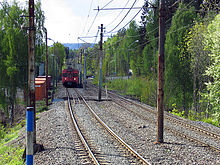 A double-track railway surrounded by trees runs down the middle of the image. On the left track is worn-looking red train. Above the tracks are overhead wires.