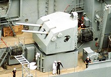 A grey turret with two gun barrels pointing forward. A black eagle, globe, and anchor insignia has been painted on the side of the turret.