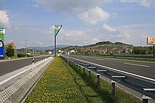 A view of the motorway next to a rest area, with a rest area sign in the background