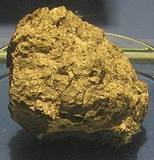 A rough-hewn rock with a yellowish sheen.