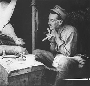 "George Wootten - ""Rest Gully"", Gallipoli. June 1915. Captain George Wootten, Adjutant, 1st Infantry Battalion, shaving at the entrance to his dugout."