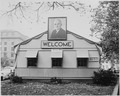 "A large photograph of President Harry S. Truman and a ""Welcome"" sign beneath it, on the side of the temporary... - NARA - 199952.tif"