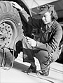 A member of the Auxiliary Territorial Service (ATS) tests the air pressure of the tyre on a large lorry as part of her driver training course in 1942. D6980.jpg
