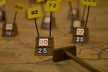 A wooden marker on a map, surrounded by several others. Below and to the right is a cue with a wooden slab on the end, used to move the markers.