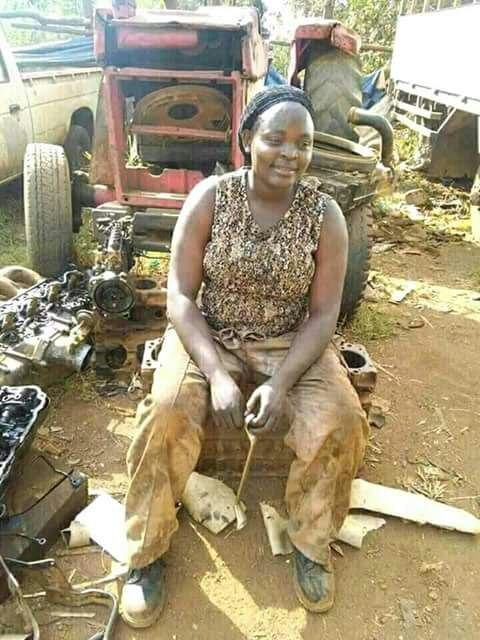 An african lady working at a garage. She is a mechanic