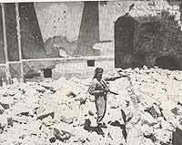 A sepia photograph shows a soldier, gun in hand, standing amidst the rubble of the destroyed synagogue. Behind him, remnants of the eastern wall show a painted fresco of Mount Sinai and two arched tablets symbolising the Ten Commandments.
