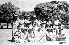 A group of soldiers in slouch hats pose with a Japanese flag