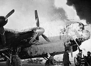 Operation Bodenplatte - Fire crews attempt to save an Avro Lancaster from burning at Melsbroek, Belgium. This aircraft had landed at Melsbroek with the number 3 (starboard inner) engine out of action, its propeller feathered.