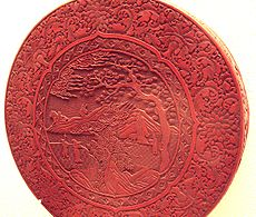 A Ming Dynasty red lacquer box with intricate carving.