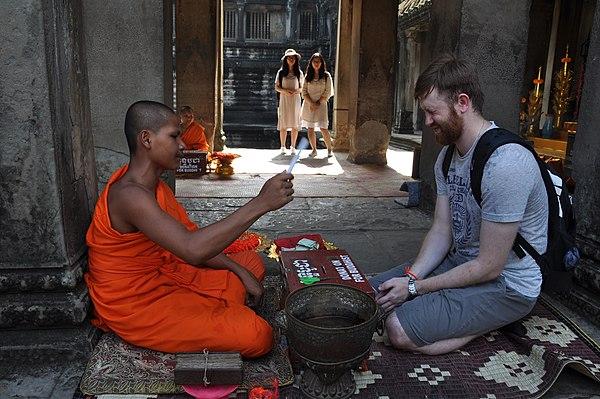 Buddhist monk and tourist at Angkor Wat.jpg