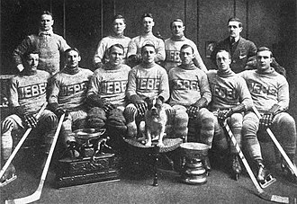 Paddy Moran (ice hockey) - The Quebec Bulldogs team after their second consecutive Stanley Cup victory; Moran is seated third from the left, next to Joe Malone, and between the O'Brien Cup and the bulldog.