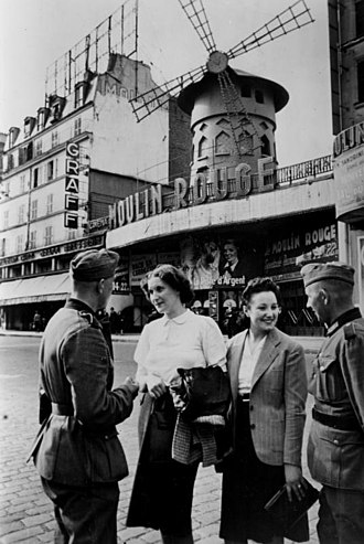 German military administration in occupied France during World War II - German soldiers talking with French women by the Moulin Rouge in June 1940, shortly after the German occupation of Paris