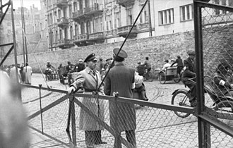 Warsaw Ghetto - Two Jewish Ghetto policemen guarding the gates of the Warsaw Ghetto, June 1942 Żelazna Street (looking South) from the intersection with Chłodna Street. In the back buildings from the left: Żelazna 75, Żelazna 75a and Chłodna 25. This section of Żelazna Street was connecting Little and Big Ghetto. This side of the gate and the buildings on the other side of the wall belonged to Polish side.