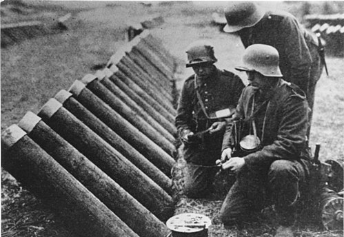 A chemical projectile being prepared by the German army on the Western Front.  With a structure similar to a simplified mortar, the enemy camp is filled with a container filled with chemicals.  (1916)